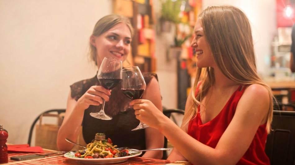 Amigas brindando con una copa de vino
